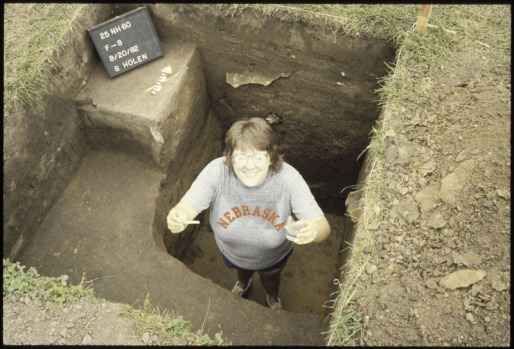 Excavated outhouse pit at Brownville Townsite. Crew member is holding a smoking pipe and whiskey glass found at bottom of the pit.